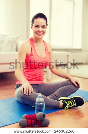 fitness, home and diet concept - smiling teenage girl with bottle of water and dumbbells after exercising at home - stock photo
