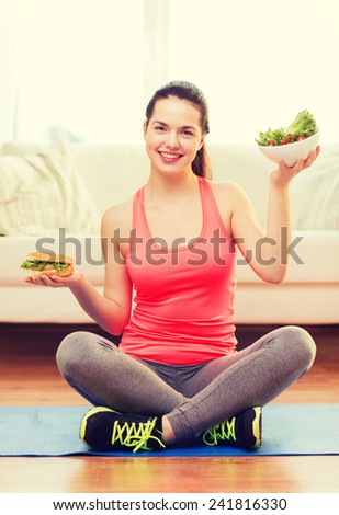 fitness, home and diet concept - smiling teenage girl with green salad and hamburger at home - stock photo
