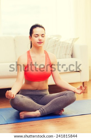 fitness, home and diet concept - smiling teenager meditating at home