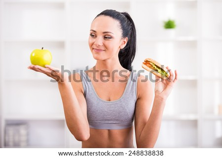 Fitness, home and diet concept. Young woman with apple and hot dog after exercising at home. Difficult choice.