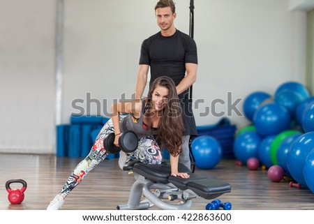Fitness instructor exercising with his client at the gym - stock photo