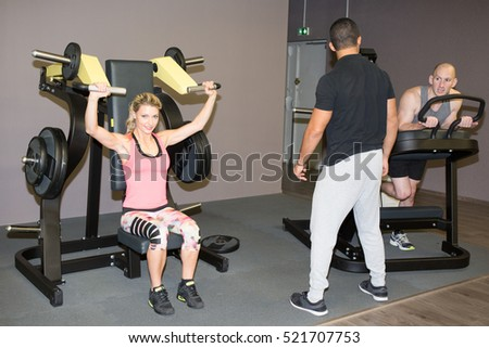 Fitness instructor exercising with his client at the gym.