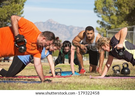 Fitness instructor with people exercising in outdoor bootcamp - stock photo