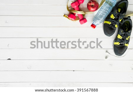fitness items on wooden planks background top view with text space - stock photo