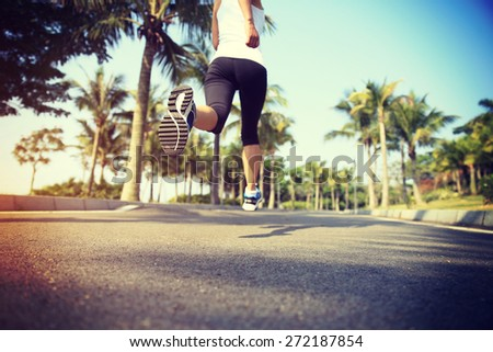 fitness jogger legs running at tropical park. woman fitness jogging workout wellness concept.  - stock photo