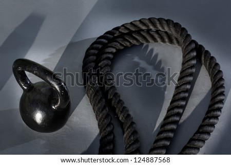 Fitness Kettlebell and battle rope on the gym floor - stock photo