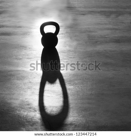 Fitness Kettlebell weight backlight and shadow on the gym floor - stock photo