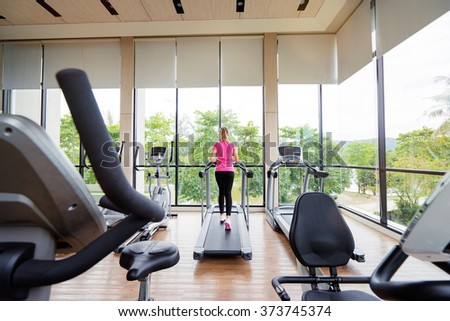 Fitness lifestyle. Young sporty woman exercising in light sport gym interior. - stock photo