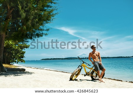 Fitness Male Model With Bike Sunbathing On Sun, Enjoying Summer Travel Vacation. Handsome Sexy Man In Sunglasses With Muscular Body, Healthy Tan Skin Tanning Near Bicycle On Sand Beach. Summertime