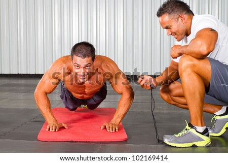 fitness man and personal trainer in gym doing push-ups - stock photo