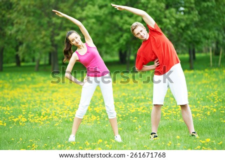 fitness man and woman doing physical stretching exercises during outdoors sport training - stock photo