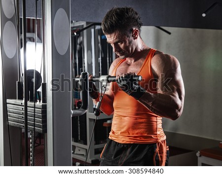 fitness man bodybuilder with muscular torso workout with dumbbells in gym - stock photo