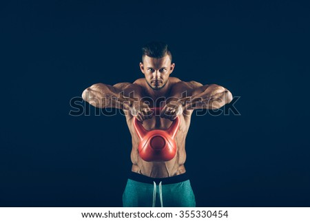 Fitness man doing a weight training by lifting a heavy kettlebell. - stock photo