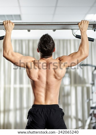 Fitness man doing pull-ups in a gym for a back workout - stock photo
