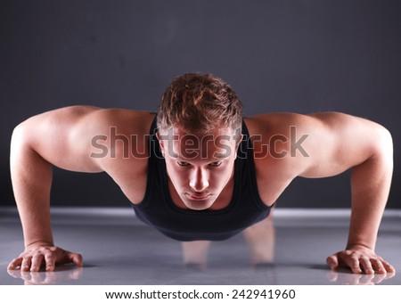 Fitness man doing push ups on floor - stock photo