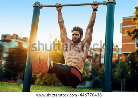 Fitness man doing stomach workouts on horizontal bar outdoors - stock photo