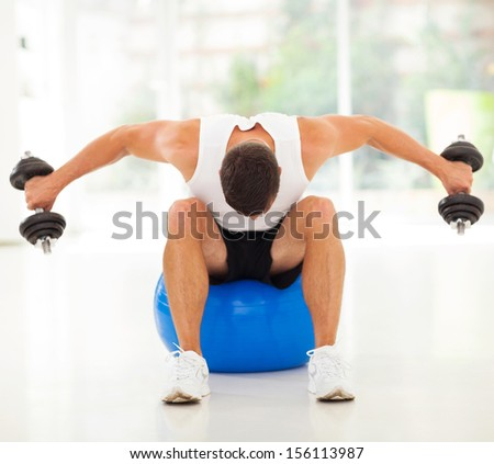 fitness man exercising with dumbbells sitting on gym ball