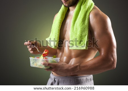 Fitness man holding a bowl of fresh salad on black background - stock photo