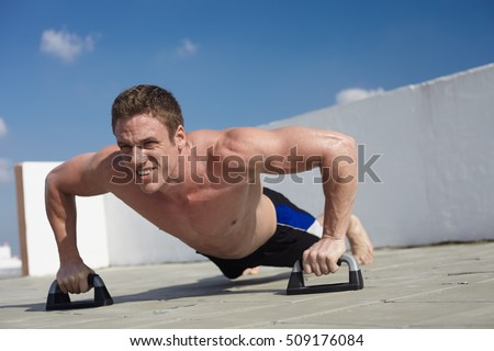 Fitness man just in one shorts do push ups out the door under blue sky