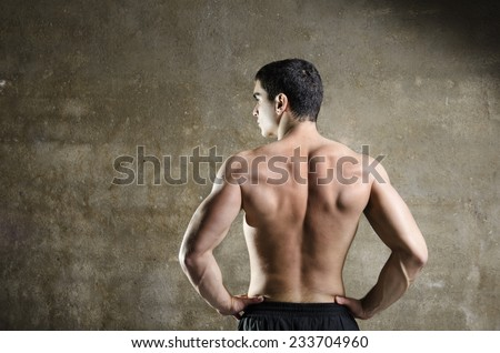 Fitness man posing with naked torso on dirty wall background