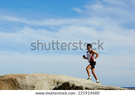 Fitness man running outdoors with high speed, sportsman on the morning jog runs over sea rocks - stock photo