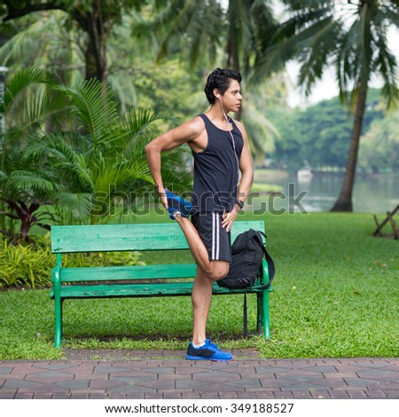 Fitness man stretching after running inside city park. Athlete exercising outdoor in Lumpini Park, Bangkok. Full body portrait.