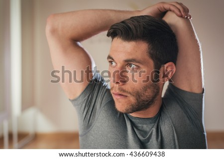 Fitness man stretching triceps before gym workout. Sporty strong male athlete standing indoor warming up arms. - stock photo