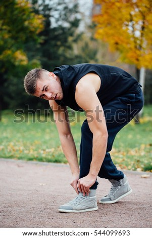 Fitness man tie shoelaces in the fall park. Looking at camera