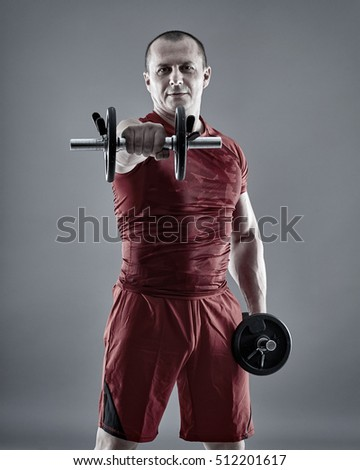 Fitness man training delts with dumbbells on gray background