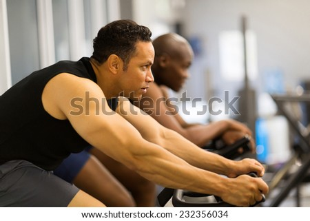fitness men working out with stationary bike in gym - stock photo