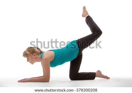 Fitness model exercising, kneeling down on all fours with one leg raised in the air towards the ceiling, in a yoga pose, isolated on white. - stock photo