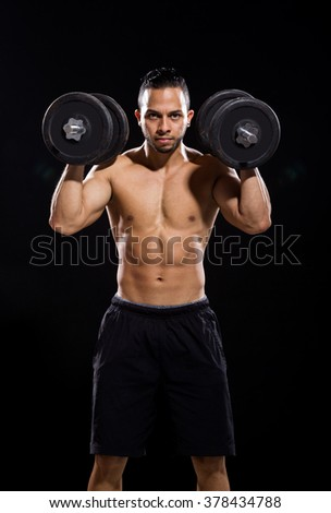 fitness model holding dumbbell on black background - stock photo