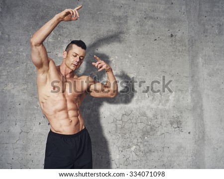 Fitness model posing showing abdominal muscles, fitness concept professionel male fitness model, copy space