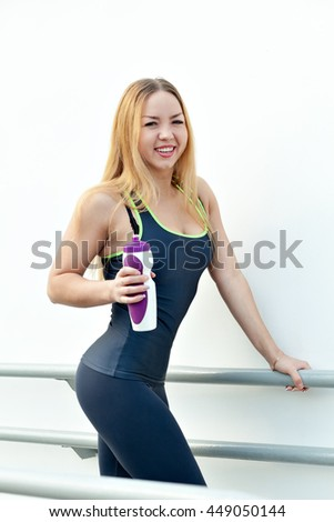 Fitness model standing and smiling against a white wall