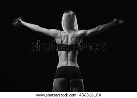 Fitness motivation. Fitness woman with dumbbell standing with her back on a black background. Perfect female sports figure. Fitness woman posing in the studio. Fitness photo in studio. Fitness bikini