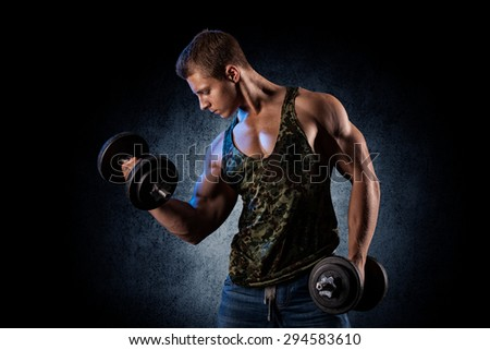 Fitness muscular body on dark background. - stock photo