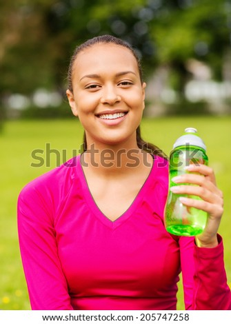 fitness, park, drink and sport concept - smiling african american woman sitting and holding bottle outdoors - stock photo