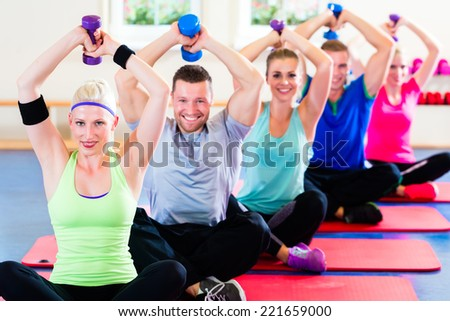 fitness people in gym working out with dumbbells