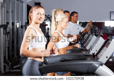 fitness people running on treadmill in gym - stock photo