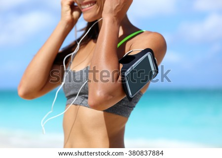 Fitness phone armband runner woman putting earphones. Closeup of sports smartphone case holder touchscreen strap on female arm of person wearing headset for running exercise cardio workout on beach. - stock photo
