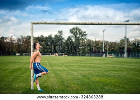 Fitness player working out on football field. Cross fit training outdoors on a sunny summer day.  - stock photo