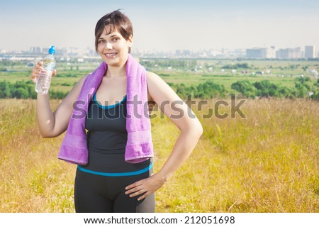 Fitness plus size woman with towel and water bottle - stock photo