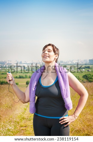 Fitness plus size woman with towel listening music outdoor in summer