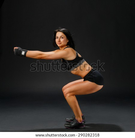 Fitness pose - young sportive woman in gym suit shows squatting in studio at black background - stock photo