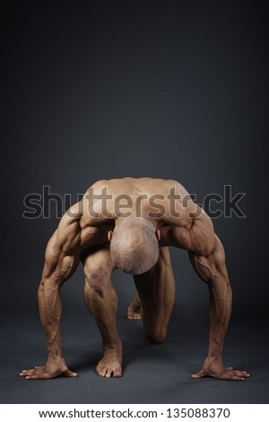Fitness - powerful muscular man lifting weights / Muscular man with dumbbells on black background - stock photo