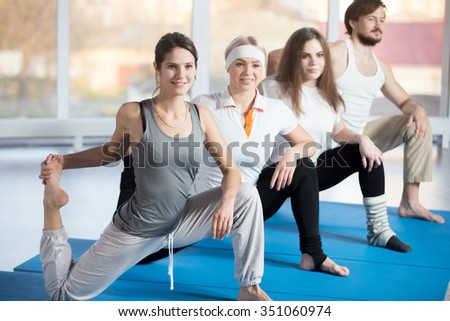 Fitness practice, group of four beautiful happy fit young people working out in sports club, doing warming up exercises, low lunges, Kneeling Quadriceps Stretch with Raised Foot on blue mats - stock photo
