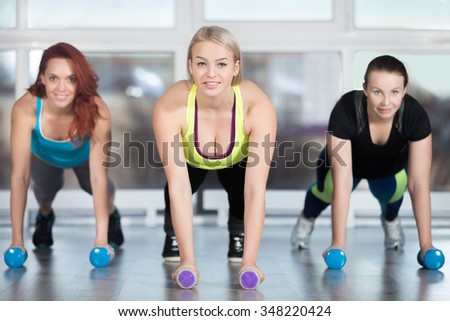Fitness practice, group of three cheerful smiling beautiful fit young females working out in sports club, doing plank exercise, using dumbbells in class, full length - stock photo