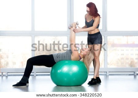 Fitness practice, two fit beautiful females working out in sports club, instructor assists blond young woman in doing exercise with dumbbells on green Swiss ball in class, full length - stock photo