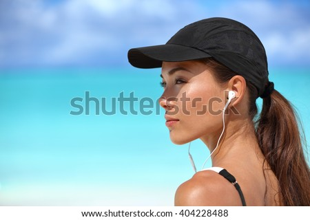 Fitness runner girl listening to smartphone music phone app on beach wearing earphones earbuds and running cap for sun protection. Asian woman healthy and active on summer vacation.  - stock photo