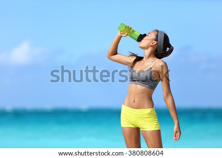 Fitness runner woman drinking water or energy drink of a sport bottle. Athlete girl taking a break during run to hydrate during hot summer exercise on beach. Healthy active lifestyle. - stock photo